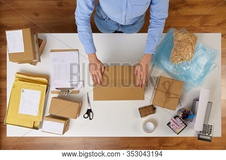 delivery, mail service, people and shipment concept - close up of woman packing parcel box with adhesive tape at post office