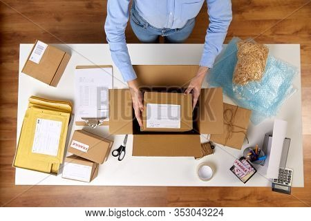 delivery, mail service, people and shipment concept - close up of woman packing parcel boxes at post office