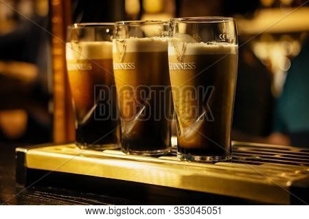 Dublin, Ireland, December 2017 Selective Focus On Three Pints Of Guinness In Glasses On Bar Or Tap.