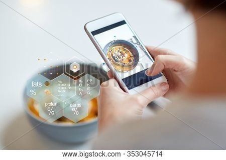 food, new nordic cuisine, technology, eating and people concept - close up of hands with bowl of vegetable pumpkin-ginger soup on smartphone screen and nutritional value chart at restaurant