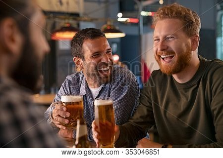 Smiling carefree friends enjoying drinking together in bar. Group of happy young men drinking cold draft beer, chatting and having good time at pub. Laughing men on night out drinking beer on counter.