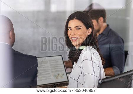 Smiling mature business woman sitting in conference room during presentation, looking at camera. Mid latin businesswoman in board room looking behind window glass during brainstorming with associates.