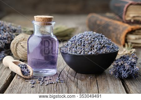Dry Lavender Flowers In Bowl And Bottle Of Essential Lavender Oil Or Infused Water. Old Books And La