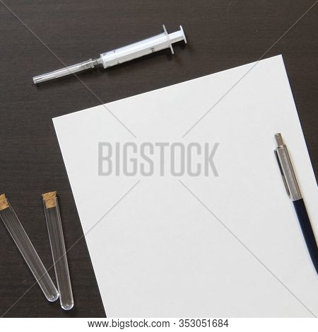 Template Of White Paper With Pen And Syringe For Injection On Dark Wenge Color Wooden Background. Th
