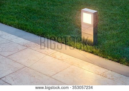 Ground Lamp Lighting Marble Walkway In The Evening Park With A Green Lawn, Closeup Lantern Illuminat