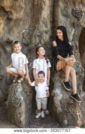 Beautiful Mother With Her Three Happy Joyful Cute Kids Sitting On The Tree Stem In The Park. Concept