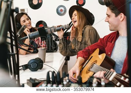 Cheerful band of young musicians playing their song at the radio room with a radio host, radio broadcast
