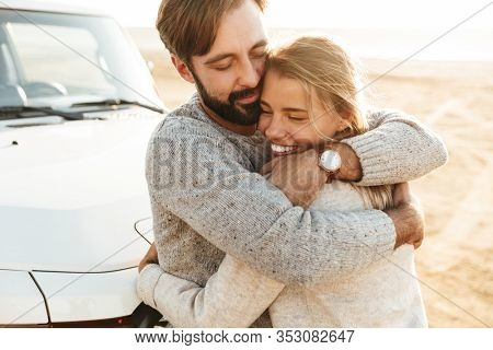 Close up of a happy young couple in love embracing while leaning on a car at the sunny beach