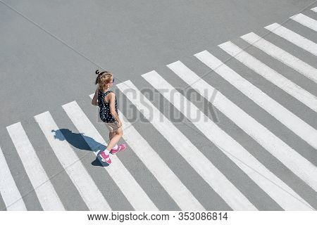 Stylish Child In Sun Glasses, Fashion Clothes Walking Along Summer City Crosswalk. Kid On Pedestrian