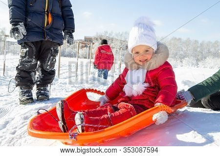 Winter Activities For Children. A Little Girl In A Red Coat Sits On An Orange Sled Before Descending