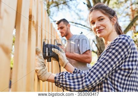 Young handyman couple at the fence grind in the garden of the new house as a home