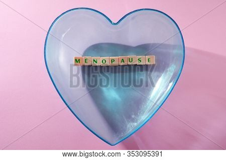 menopause word written on square block in a heart shape container. menopause text on pink  background