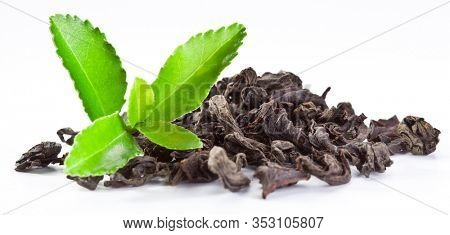 Dried tea leaves with fresh green tea leaves isolated on a white background.