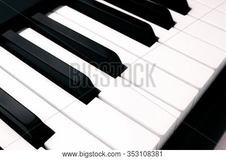 Close-up Side View Of Synthesizer On White Background. Digital Keyboard. Musical Instrument. Black A