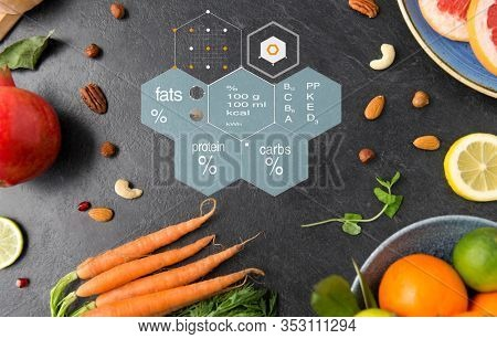 healthy eating, food and diet concept - different vegetables and fruits on on slate table over nutritional value chart