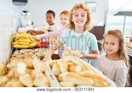 Students in elementary school take fruit at the buffet in the cafeteria