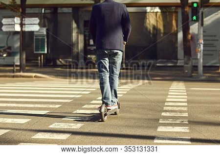 Legs Of A Man In Jeans And Sneakers On An Electric Scooter At A Crosswalk On A City Street