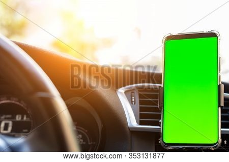 Modern Smartphone Device Gadget Mounted On Phone Holder At Car Dashboard. Mock-up Green Chroma Key S