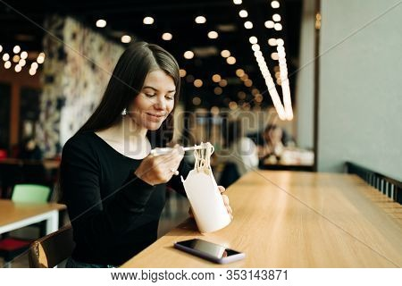 Lifestyle portrait of Real Young pretty woman, eating chinese food with chopsticks