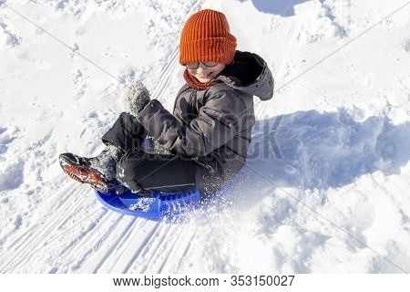 A Teenager Flies On A Round Sled From A Hill. White Snow Scatters To The Sides. Winter Games For Chi
