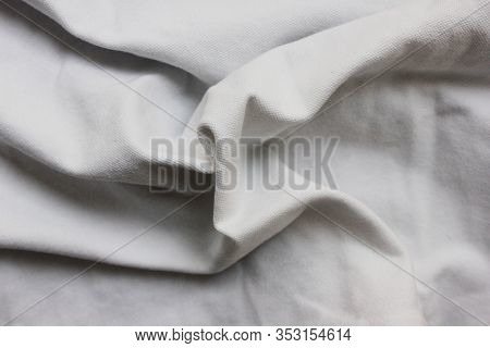 Wrinkled White Linen Bed Sheet, Crumpled Fabric Texture Of Clean Cloth Background. Soft Wavy Worn Cl