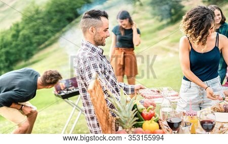 Young Friends Having Fun On Outdoors Picnic Preparing Food At Barbecue Grill Party - Happy People Co