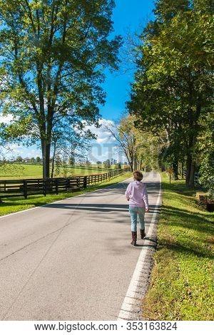 Woman Walking Country Road Along Horse Farms.