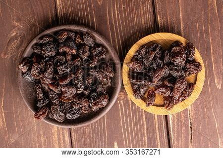 Lot Of Whole Dried Dark Raisin On Round Bamboo Coaster With Brown Ceramic Coaster Flatlay On Brown W