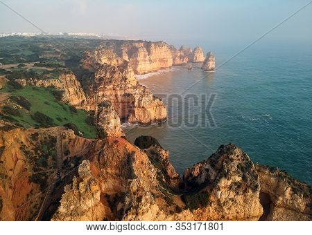 Aerial Photo Above Panoramic View Of Ponta Da Piedade Headland With Group Of Rock Formations Yellow-