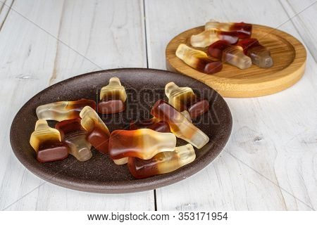 Lot Of Whole Sweet Jelly Cola With Brown Ceramic Coaster On Round Bamboo Coaster On White Wood