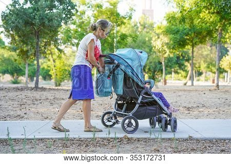 Young Mom With Baby Carriage. Woman With A Baby Carriage For Two Children Walks In The Park On A Sum