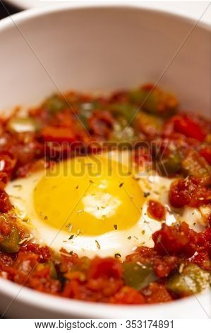 A Dish Of The Fried Egg With The Stewed Peppers