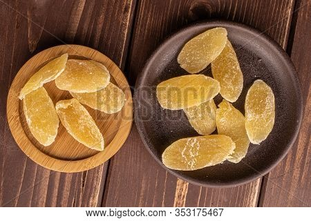 Lot Of Slices Of Dried Yellow Pineapple On Round Bamboo Coaster With Brown Ceramic Coaster Flatlay O