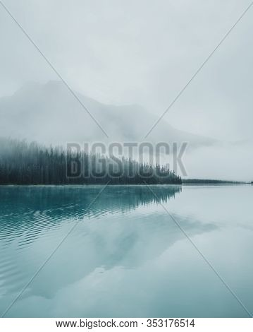 Thick, Eerie Fog Creeping Over Pine Trees With Towering Hazy Mountains Across The Emerald Water Refl