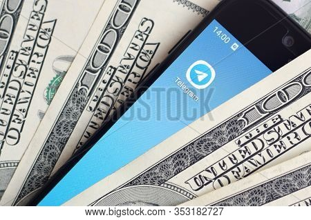Smartphone Screen With Telegram App And Lot Of Hundred Dollar Bills. Business And Social Networking