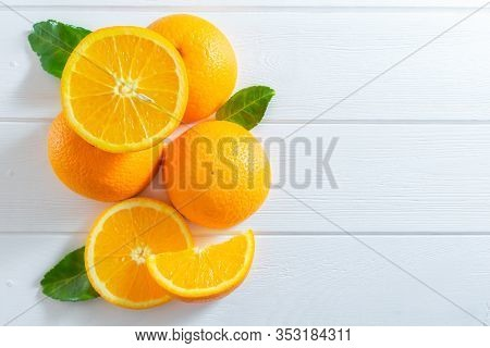 Fresh Oranges And Green Leaves On White Wooden Table. Flat-lay, Top View.