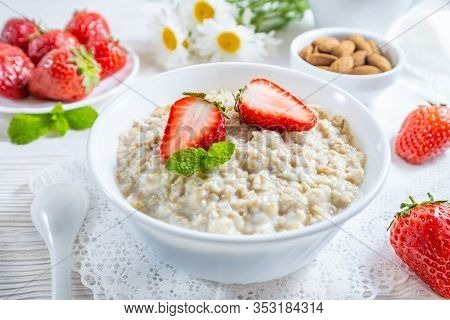 Oatmeal With Strawberry And Nuts In Bowl On White Wooden Table.