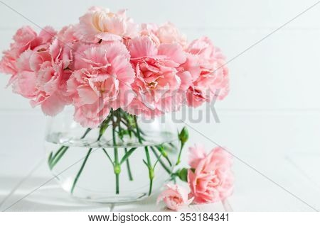Pink Carnations In Glass Vase On White Wooden Background With Copy Space.