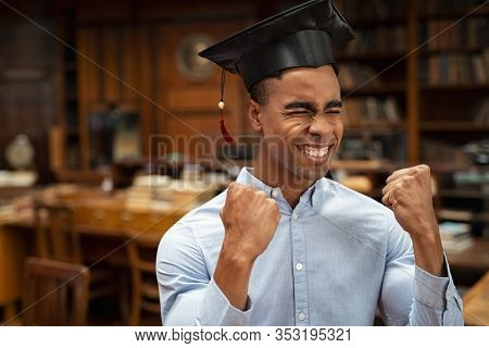 Excited graduate college student celebrating his academic success. Enthusiastic african young man feeling excited on graduation. Successful graduated guy wearing mortar board with copy space.