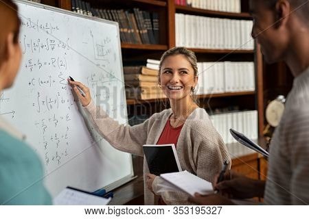 Happy girl writing math formulas on whiteboard. Young woman solving arithmetic problem with university students in classroom. Smiling college student explaining math problem at school.