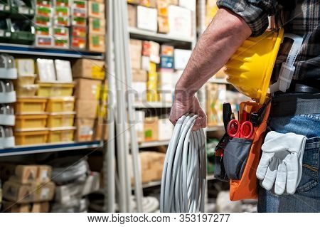 Electrician In The Electrical Component Store Holds The Roll Of Electric Cable In His Hand, Helmet W