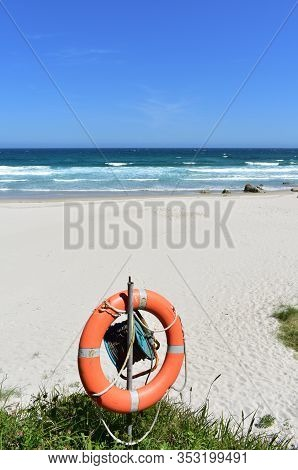 Beach With Life Saver, White Sand And Wild Turquoise Sea With Waves. Furious Sea With Foam, Sunny Da