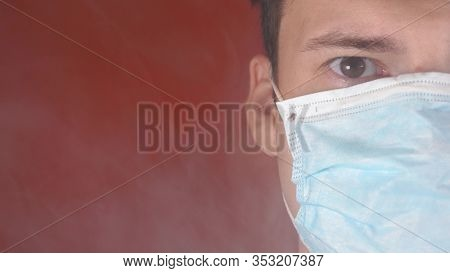 Man With Medical Mask On His Face. Close-up Of Male Part Of Face Looking In Camera. Adult Guy Covere