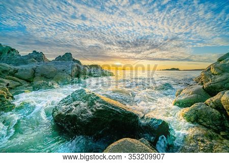 Sunrises Over Distant Horizon Along Beach From Rocky Foreground Under Altocumulus Cloud Formation On