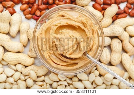 Creamy Peanut Paste, Peanut Butter In Open Glass Jar In The Center Of Peanuts Food Background. Peanu