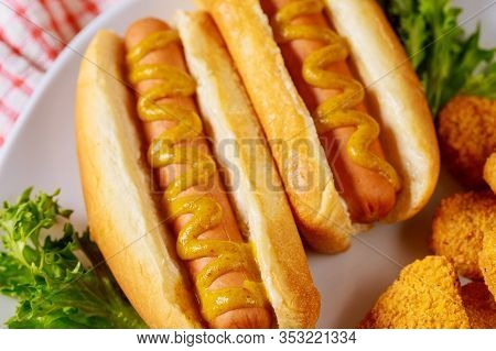 Hot Dog With Mustard On White Plate With Lettuce. Close Up.