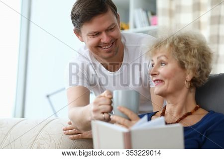 Happy Son Brought Cup Tea For An Elderly Mother. Son Cares For An Elderly Mother At Home. An Adult S