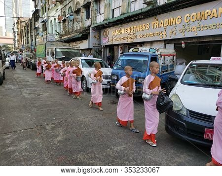 Traditional Buddhist Monks Begging In Myanmar. Child Monks In Pink Robes In The Streets Of Yangon, F