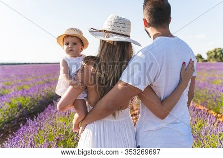 Happy Family Having Fun In A Field Of Flowers.
