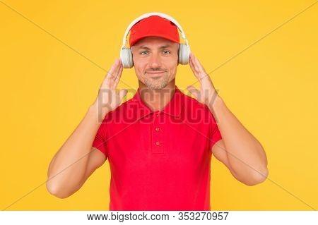 Best Sounding Headphones. Happy Guy Wear Headphones Yellow Background. Handsome Man Listen To Music